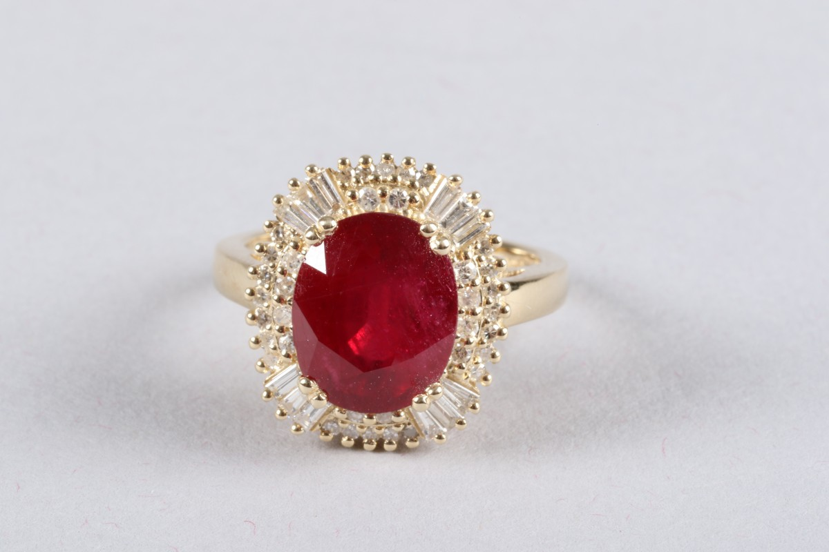 14K yellow gold and diamond ring set with an oval cut ruby, approx. 5.4 carats, diamond weight approx. 1.10 carats