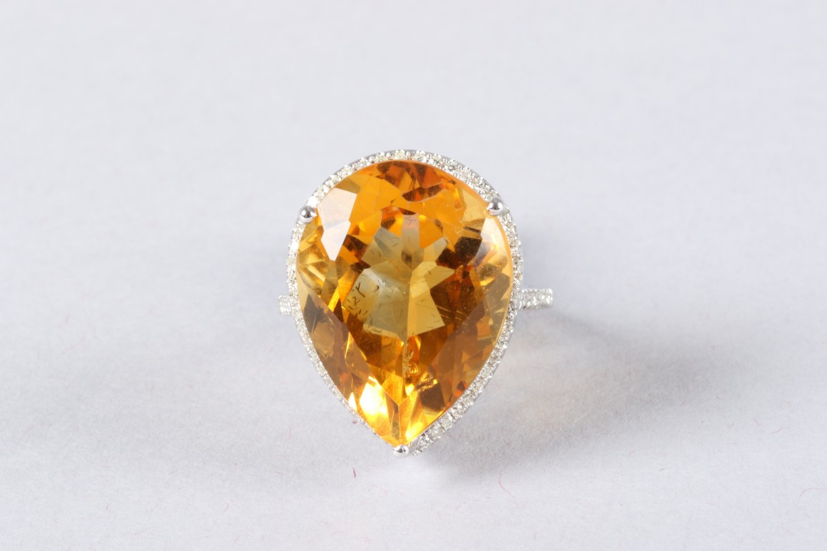 14K white gold and diamond ring set with a pear shaped citrine, approx. 13 carat, diamond weight approx. 0.5 carats